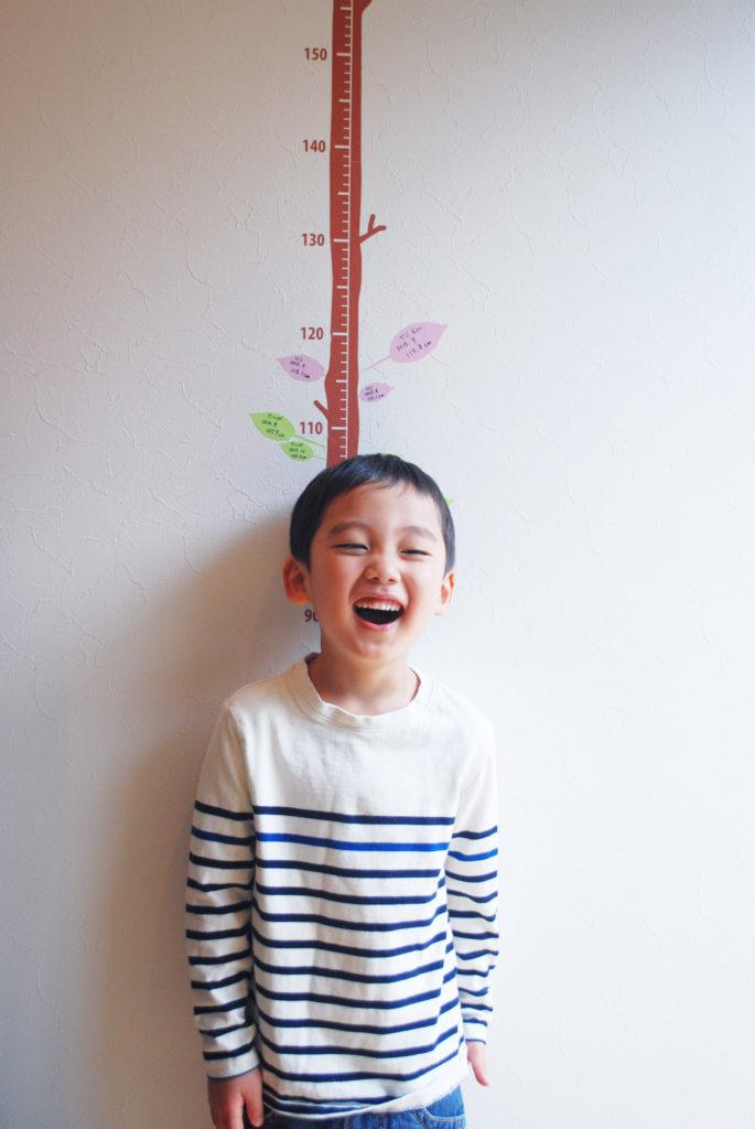 楽しそうに木の身長計ウォールステッカーで身長を計る子ども